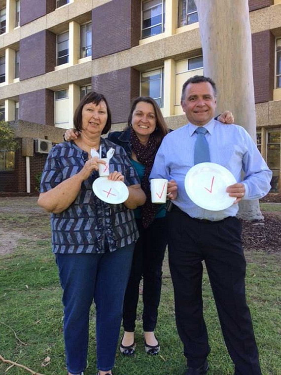 three people in front of a hospital holding up single use items like plastic plates and plastic cutlery