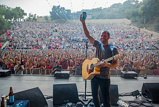 jack johnson holding up reusable cup on stage with crowd cheering in the background