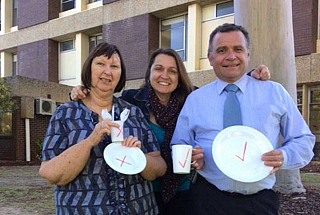 hospital staff holidng up single use items with a big red cross and reusable items with a tick