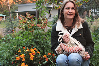 Joanna in front of her veggie garden at home