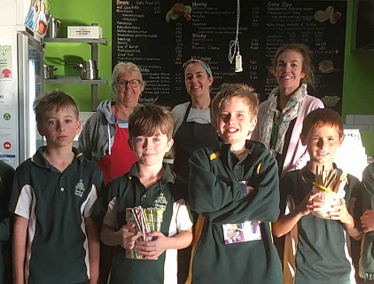 Parents and staff with students in the school canteen holding reusable items like paper straws and bamboo spoons