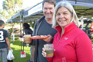 Lucie and her husband with reusable cup and plate at local farmers market