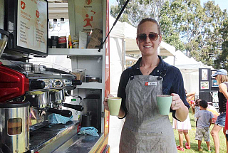 young woman working at coffee van holding two reusable mugs with coffee