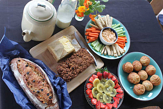 table with tea pot, loaf of bread, cake, plate with cut fruit, cut vegetables with a dip and muffins