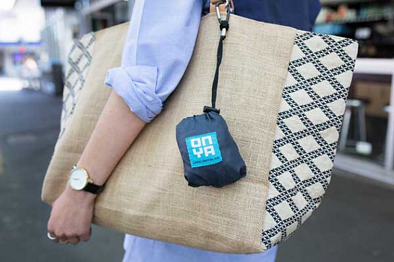 Onya shopping bag pouch is attached via a clip to a lady's handbag