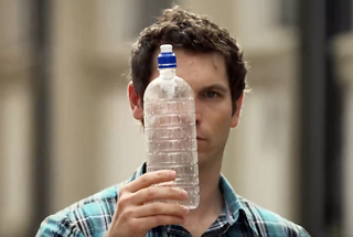 man looking at empty plastic water bottle