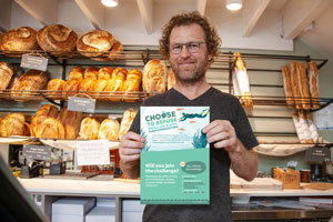 Bakery owner standing in his shop in front of shelves with bread holding up a poster for Plastic Free July reading 'Choose to refuse single use plastics – will you join the challenge?'